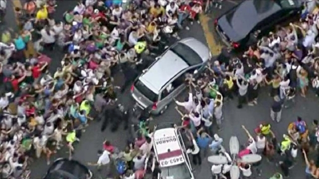 In this image from video, a crowd mobs the silver Fiat carrying Pope Francis through Rio de Janeiro on Monday. Ecstatic believers forced the closed Fiat to stop several times as they swarmed aroun ...