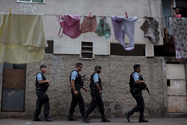 Policemen from the Pacifying Police Unit, or 'UPP', patrols in the Varginha area of the Manguinhos slum complex in advance of Pope Francis' trip to Rio de Janeiro. In one of the key events of his  ...