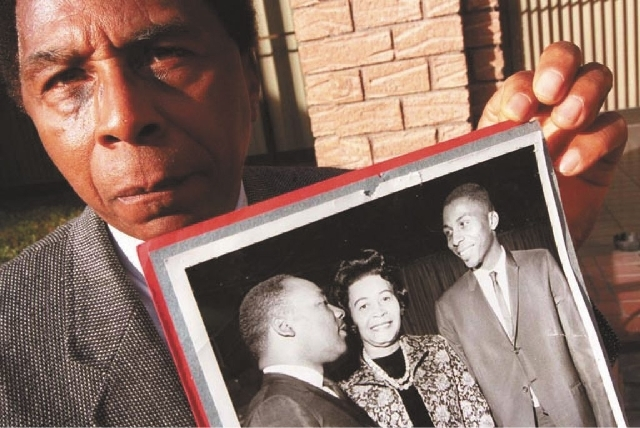 Reverend Marion Bennett holds a 1964 photo of him and Martin Luther King in this undated photo.