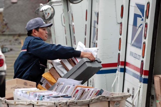 Letter carrier Diosdado Gabnat moves boxes of mail into his truck to begin delivery at a post office in Seattle in this Dec. 5, 2011, file photo. Americans for generations have come to depend on d ...
