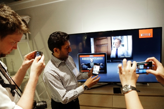 Suveer Kothari, center, displays how the new Chromecast device operates a television with the use of a smartphone during a Google event on Wednesday in San Francisco.