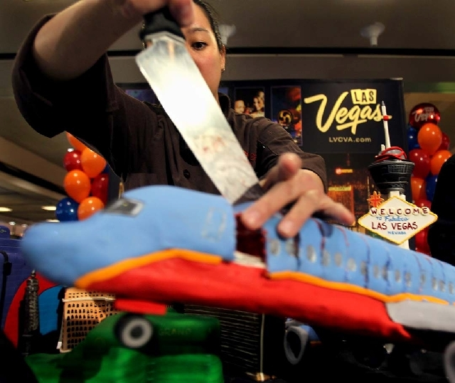 Carolyn Portuondo, with Caked Las Vegas, cuts a cake made in the likeness of a Southwest Airlines plane at McCarran International Airport in 2012 as Southwest Airlines marked its 30th anniversity  ...