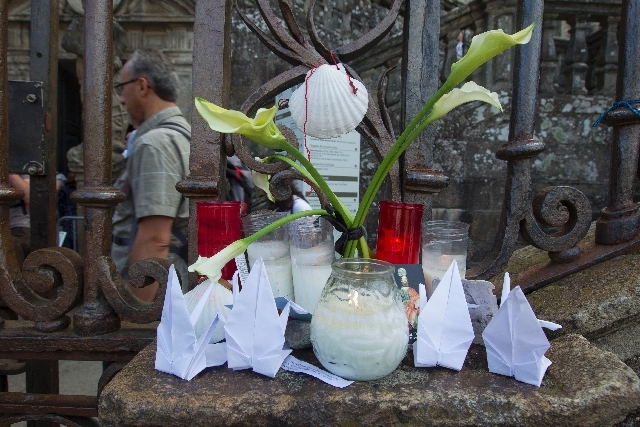 A man passes by a makeshift altar Friday outside of the cathedral for the victims of the Wednesday train accident in Santiago de Compostela, Spain.