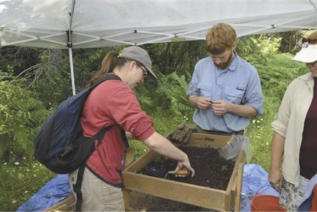 In this July 11, 2013 photo, Stacey Lynn Camp and Morgan Bingle sift through dirt excavated from in front of an incinerator at the Kooskia Internment Camp near Kooskia, Idaho.