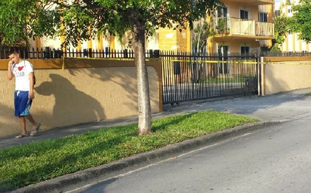 A resident of an apartment building where seven people were killed walks by police tape in Hialeah, Fla., early Saturday.