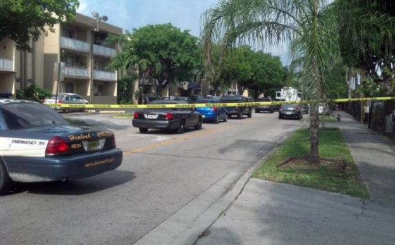 Police cars line a street where a seven were killed at an apartment building in Hialeah, Fla., early Saturday.