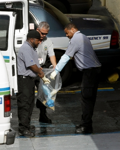 Miami-Dade morgue workers place objects in a bag outside an apartment building at the scene of a fatal shooting in Hialeah, Fla., Saturday.