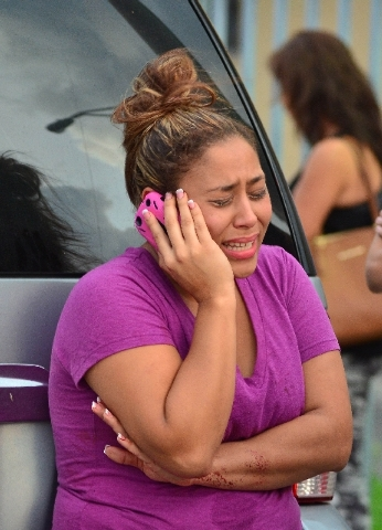 A woman talks on the phone outside an apartment building at the scene of a fatal shooting in Hialeah, Fla., early Saturday.