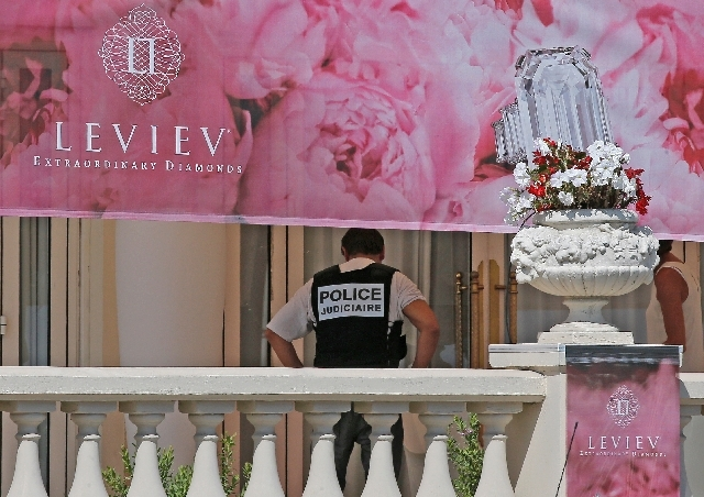 A policeman is seen at the Carlton hotel, in Cannes, southern France, the scene of a daylight raid, Sunday, July 28. A staggering 40 million euro ($53 million) worth of jewels and diamonds were st ...