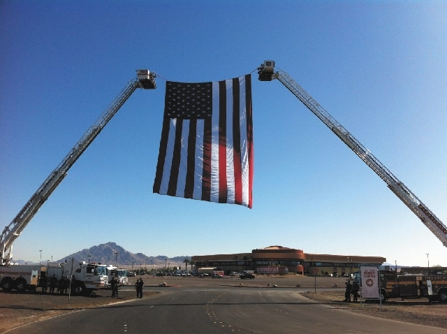 Henderson Fire Department and Las Vegas Search and Rescue suspend the U.S. flag over the main entrance to Central Christian Church on Monday for the funeral of Las Vegas officer David VanBuskirk,  ...