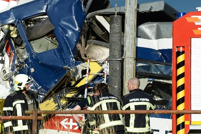 Rescue personnel work at the site where two passenger trains collided head-on in Granges-pres-Marnand, western Switzerland, Monday. Numerous people have been injured.