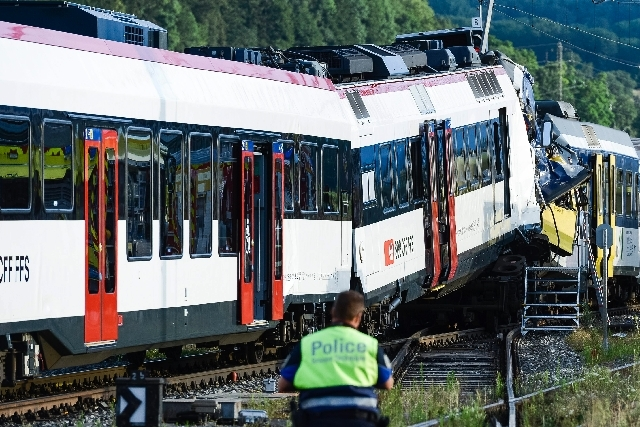 A police officer inspects the site where two passenger trains collided head-on in Granges-pres-Marnand, western Switzerland, Monday. Numerous people have been injured.