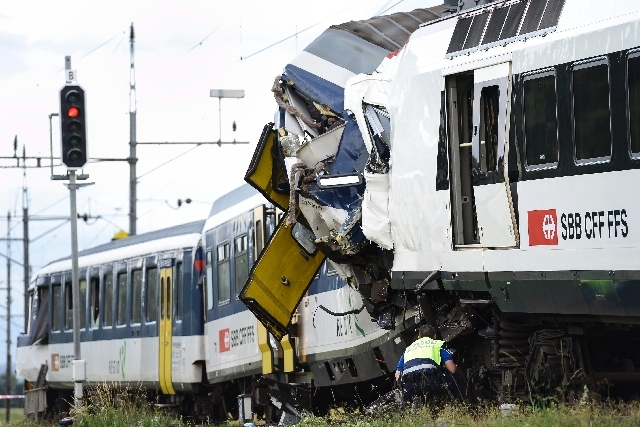 A signal shows red light as a police officer works at the site where two passenger trains collided head-on in Granges-pres-Marnand, western Switzerland, Monday. Police says that 44 people have bee ...