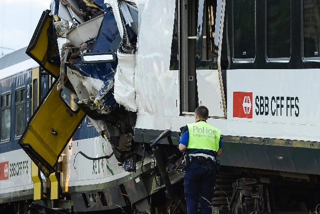 A police officer works at the site where two passenger trains collided head-on in Granges-pres-Marnand, western Switzerland, Monday. Police says that 44 people have been injured.