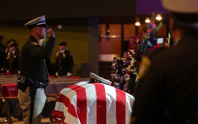 ---A Las Vegas Metro Police officer salutes the casket of search and rescue officer David VanBuskirk before the start of a visitation and funeral service, Monday in Henderson, Nev. VanBuskirk fell ...
