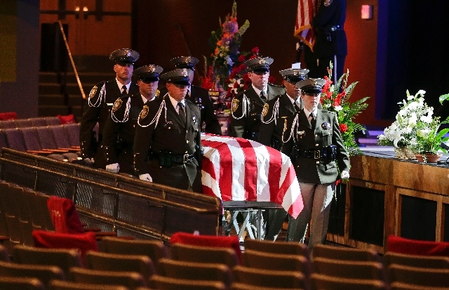 Las Vegas Metro Police officers roll the flag-draped casket of search and rescue officer David Vanbuskirk to its place inside Central Christian Church before a funeral service, Monday, July 29 in  ...