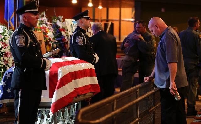North Las Vegas Police honor guard members stand at the side of the casket of search and rescue officer David VanBuskirk as a visitor pays his respects during a visitation and funeral service, Mon ...