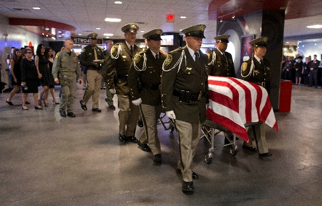 Las Vegas Metro Police officers escort the casket of search and rescue officer David VanBuskirk into the Central Christian Church for a visitation and funeral service, Monday in Henderson, Nev. Va ...