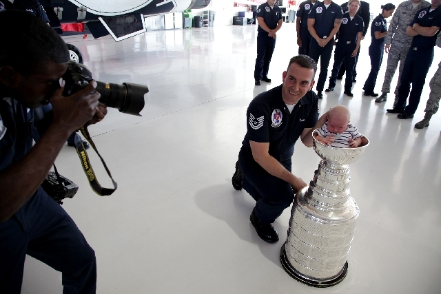 Tech. Sgt. Michael Criss poses Monday with his 1-month-old son Rhys inside the bowl of the Stanley Cup in the Thunderbirds Hangar at Nellis Air Force Base in Las Vegas.
