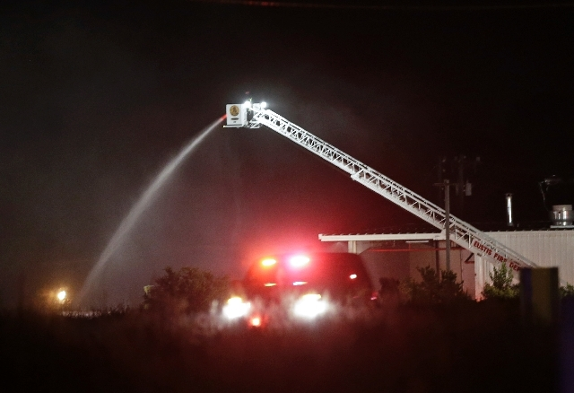 Fire crews pour water on a fire early Tuesday morning after an explosion at the Blue Rhino propane gas company in Tavares, Fla. John Herrell of the Lake County Sheriff's Office said there were no  ...
