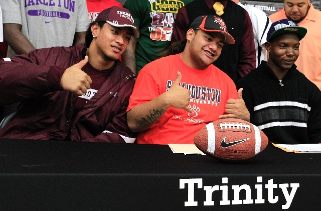 In this Feb. 1, 2012 file photo, Polo Manukainiu, left, Sione Latu, center, and Dez Richardson gesture after their signing ceremony at Trinity High School in Euless, Texas. Texas A&M officials say ...