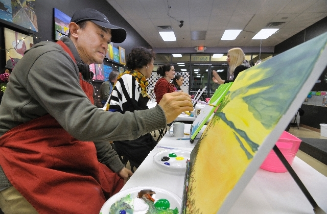 Adam Wang works on a landscape painting during a 2012 class at the Paint and Party art studio, 8826 S. Eastern Ave.