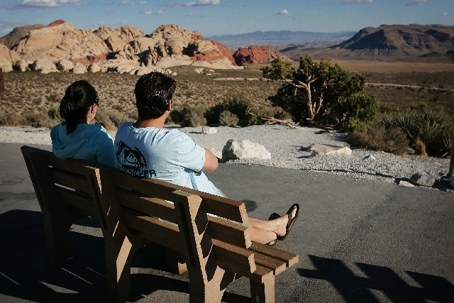 A couple sit on a bench overlooking Red Rock Canyon National Conservation Area.