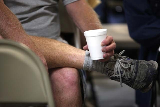 A client who didn't wish to be identified clasps a styrofoam cup of water while watching a movie at the cooling station at Catholic Charities of Southern Nevada in Las Vegas in this Aug. 23, 2011, ...