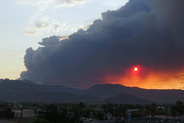 The setting sun is seen through the smoke column of the Carpenter 1 Fire on Mount Charleston from the corner of Tenaya Way and Cheyenne Avenue in Las Vegas on July 5.