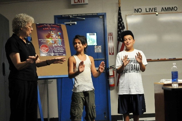 From left, gun safety instructor Gwen Eaton performs the Eddie Eagle gun safety dance with 12-year-old Justice Claveria and 10-year-old Joshua Reynolds during a July 12 class at The Gun Store, 290 ...