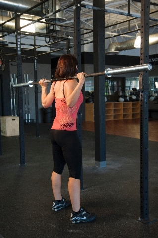 BARBELL SQUAT, START: While the bar is resting on the rack, grip the bar at a comfortable width. Dip under the bar and position it on the meat of the upper back (high bar or low bar). Straighten t ...