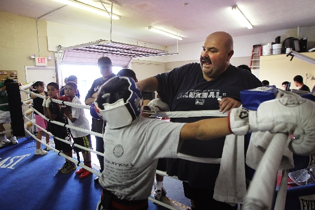 The family of North Las Vegas Center Ring Boxing CEO Jose Banales, right, shown Thursday advising 11-year-old Jonathan Aguilar, founded the club in a garage in 1994.