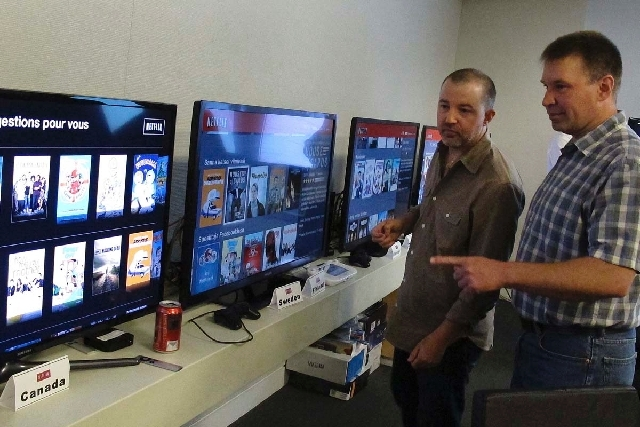 """Chris Jaffe, Netflix VP of Product Innovation, left, and Bob Heldt, Director of Engineering, look over video displays as they await the debut of """"Orange is the new black"""" in Los Gatos, Calif., on  ..."""