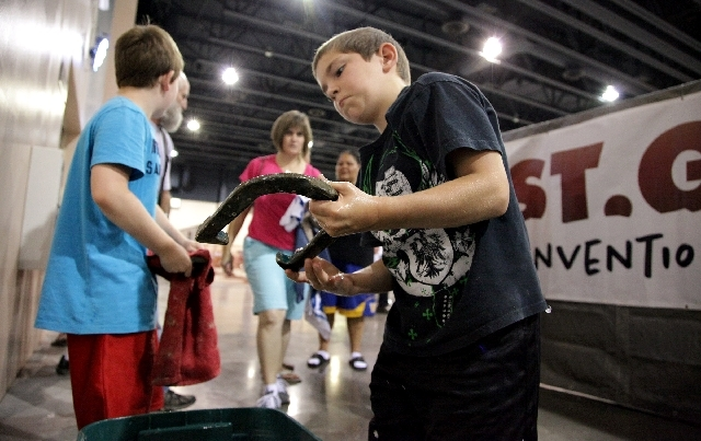 Colhyn Turner, 9, of Woodstock, Kan, washes a competitor's horseshoe Wednesday during the National Horseshoe Pitchers Association World Tournament at St. George, Utah.
