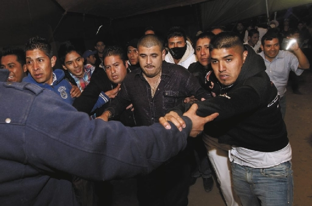 """In this 2011photo, singer Alfredo Rios, known as """"Komander"""" is surrounded by his security team after performing in concert at a rodeo in Naucalpan, Mexico. Rios is the king of Movimiento Alterado, ..."""