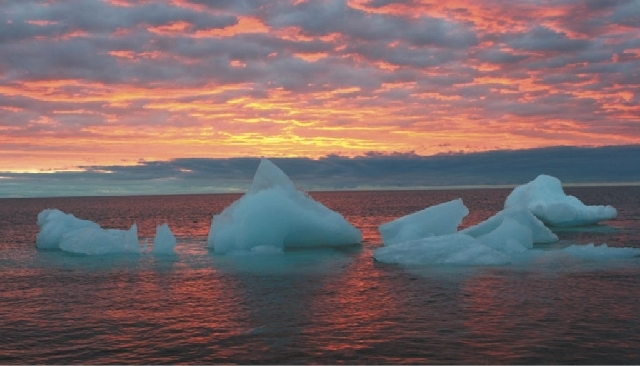 In this Sept. 13, 2006 file photo, ice chunks float in the Arctic Ocean as the sun sets near Barrow, Alaska. For the first time since May, the sun has set in what is billed as the northernmost cit ...