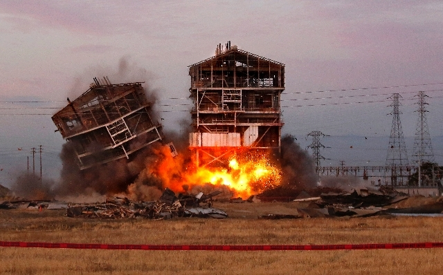 An explosion knocks down one of the remaining towers at the old Kern Power Plant,  Saturday in Bakersfield, Calif. Five spectators were injured  after shrapnel was sent flying at the demolition of ...