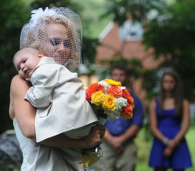 Christine Swidorsky carries her son and the couple's best man, Logan Stevenson, 2, down the aisle to her husband-to-be, Sean Stevenson, during the wedding ceremony on Saturday in Jeannette, Pa. Lo ...