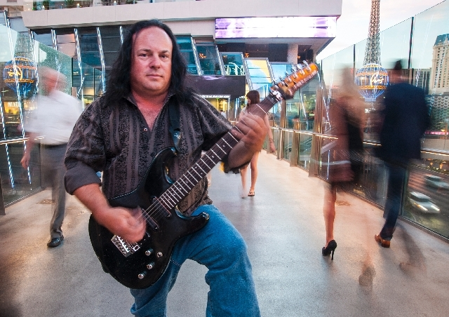 Street performer Michael T. Moore, 46, poses for a portrait on the walking bridge between the Cosmopolitan and the Aria on Friday. Moore who plays the electric guitar, had his amplifier confiscate ...