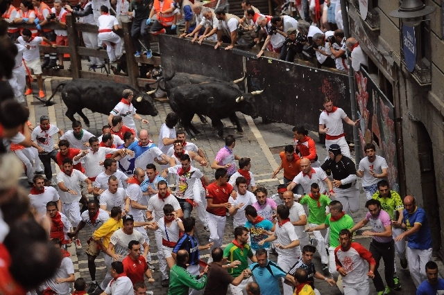 Participants run ahead of fighting bulls Saturday at the San Fermin festival in Pamplona, Spain. Revelers from around the world take part in some of the eight days of running of the bulls made fam ...