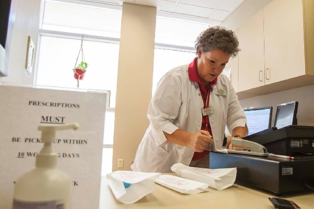 Senior pharmacist Anne Hartig takes a prescription from a client of the University of Nevada, Las Vegas pharmacy,  located inside UNLV's Student Health Center. The on-campus pharmacy offers studen ...