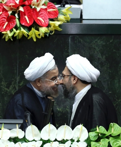Iran's new President Hasan Rouhani, left, and judiciary chief Sadeq Larijani greet each other Sunday after Rouhani was sworn in at the parliament in Tehran.