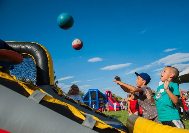 Cousins Angelo Marquez, 9, left, and Pablo Sanchez, 6, shoot basketballs during the Andson Foundation's Back 2 Class Bash on Saturday at Goett Family Park, in the Southern Highlands community of L ...