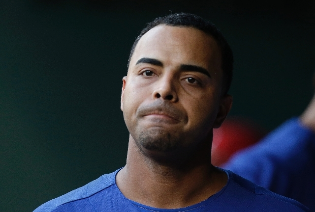 In this July 21, 2013 file photo, Texas Rangers right fielder Nelson Cruz walks in the dugout during a baseball game against the Baltimore Orioles in Arlington, Texas. Major League Baseball has to ...