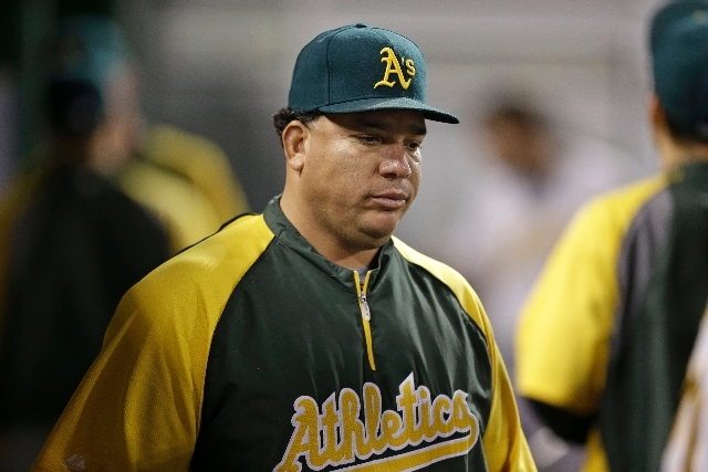 In this July 11, 2013 file photo, Oakland Athletics starting pitcher Bartolo Colon stands in the dugout during the ninth inning of a baseball game against the Pittsburgh Pirates in Pittsburgh. Maj ...