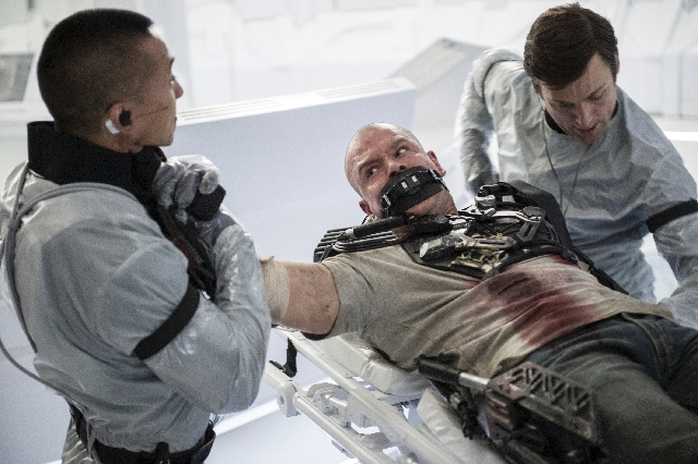 "This film publicity image released by TriStar, Columbia Pictures-Sony shows Matt Damon, center, in a scene from ""Elysium."""