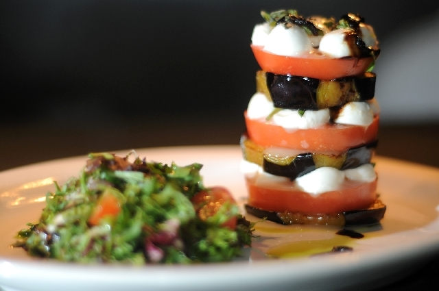 A caprese with sliced tomatoes, grilled marinated eggplant, mozzarella cheese, basil and extra virgin olive oil is served with a side of spring green mix.