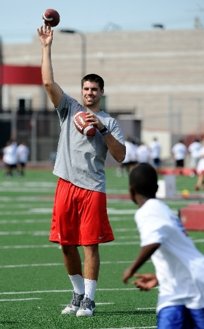 UNLV quarterback Nick Sherry lobs a pass to a youngster during a youth football camp Monday at Rebel Park, where the team will begin training camp at 8 a.m. Tuesday. Sherry, a sophomore, is coming ...
