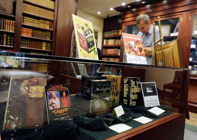 "A visitor looks over the exhibit of first-edition books titled ""Before They Were Movies"" at Bauman Rare Books. Among criteria that determines the value of first-edition books are their condition,  ..."