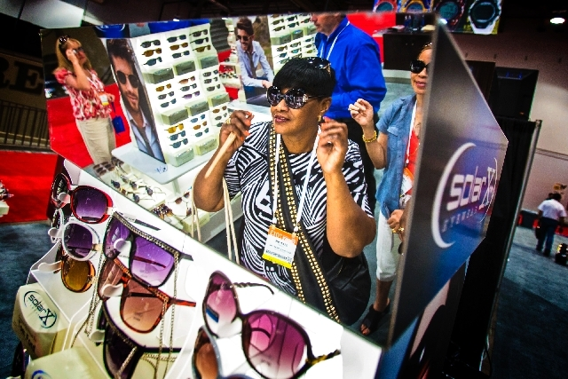 Glennie Gaines tries on glasses Monday at the SolarX Eyewear booth at the ASDLV show in the Las Vegas Convention Centery.
